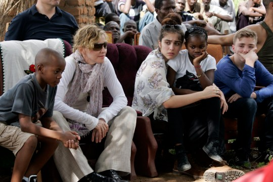 US Pop Star Madonna (2nd L) sits with her biological and adopted children (L to R) David Banda, Lourdes, Mercy James, and Rocco at Mkoko Primary School, one of the schools Madonna's Raising Malawi organization has built jointly with US organization BuildOn, during the visit of Madonna on April 2, 2013 in the region of Kasungu, central Malawi. Madonna, said to be the single largest international philanthropic donor to Malawi, also supports childcare in the country which is home to nearly a million children orphaned by AIDS. She arrived in Malawi on March 31 with the two children she adopted from the small landlocked African country. AFP PHOTO / AMOS GUMULIRA (Photo credit should read AMOS GUMULIRA/AFP/Getty Images)