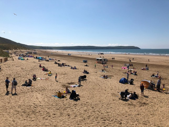 Holidaymakers enjoy the sun at Woolacombe in North Devon, as temperatures are set to soar again following a week of bad weather.