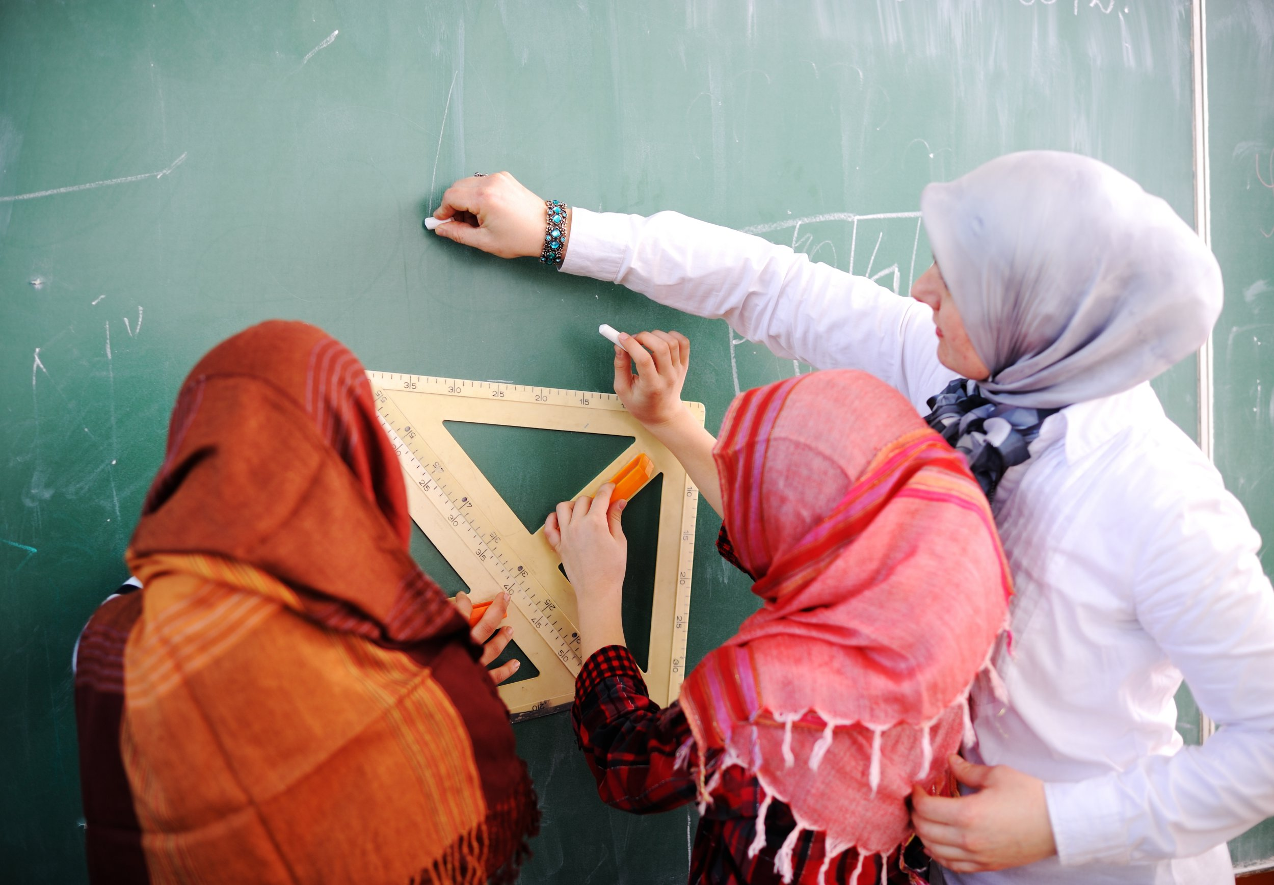 Arabic Muslim teacher showing school girls on the classroom board
