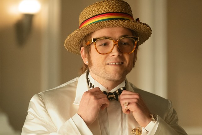 Taron Egerton as Elton John adjust his bowtie in the biopic movie Rocketman