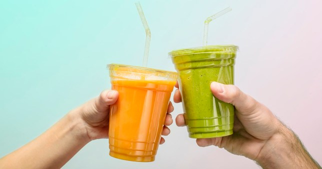 Young man and woman's hands toasting with fruit and vegetable smoothies in plastic cups