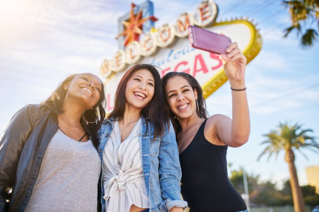 all girl group of friends having fun taking selfies in front of welcome to las vegas sign shot with lens flare