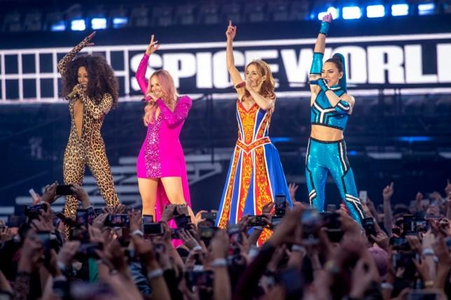 Mel B, Emma Bunton, Geri Halliwell and Melanie C of The Spice Girls singing on stage during tour