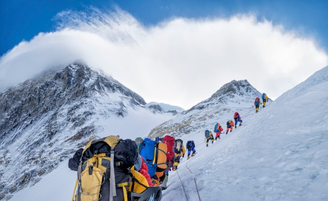 Climbers hiking up Mount Everest to join the queue to the top