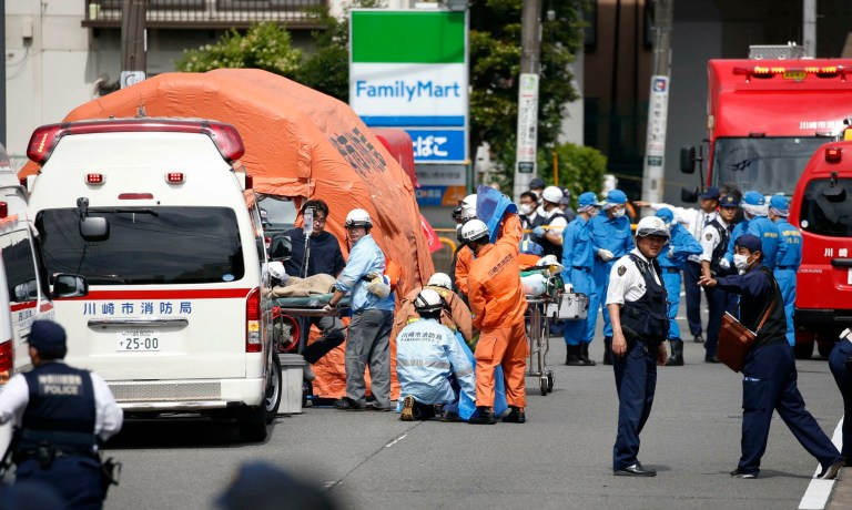 Rescuers work at the scene of the attack in Kawasaki, near Tokyo after a man wielding a knife attacked commuters waiting at a bus stop