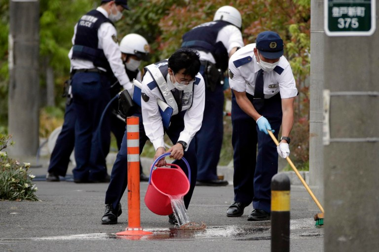 Police officers clean the scene where a man wielding a knife attacked commuters May 28, 2019, in Kawasaki