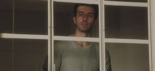 Rafael (Justin Baldoni) stares through a window in Jane The Virgin