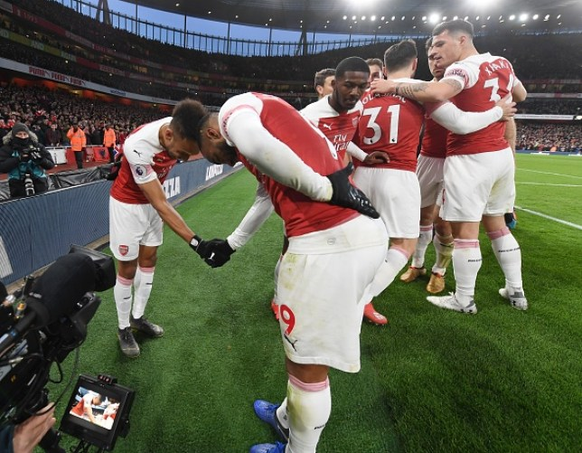 Arsenal players Alexandre Lacazette and Pierre-Emerick Aubameyang shaking hands in front of teammates on the pitch