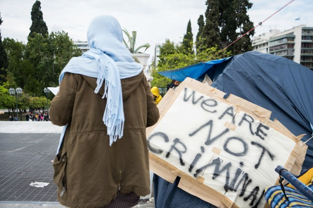 Woman wearing a headscarf standing next to a tent that has a sign which says 'We are not criminal'