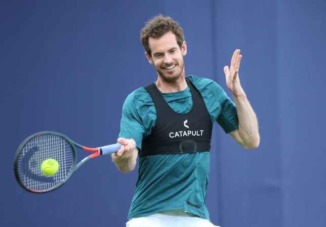 Andy Murray smiles as he hits a forehand at Queen's
