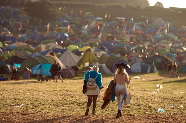 Festival-goers prepare to leave the site at the end of the Glastonbury Festival with tents in front of them