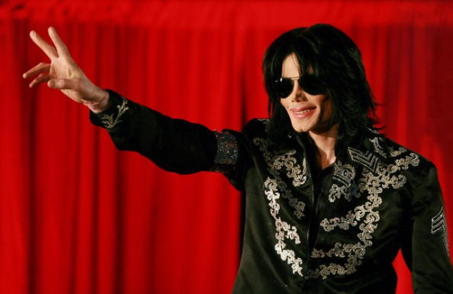 MIchael Jackson raising his hand up in front of a red curtain at a press conference at the O2 Arena in London