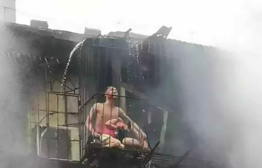 Pic Shows: The dad and his 4-year-old daughter who survived the fire; CHINA: This footage shows a desperate couple shielding their young daughter from a fire in their flat while helplessly trapped outside their window by their burglar bars.