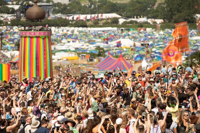 Festival goers enjoy the sun as they dance and listen to music at the Glastonbury Festival at Worthy Farm, Pilton, Somerset