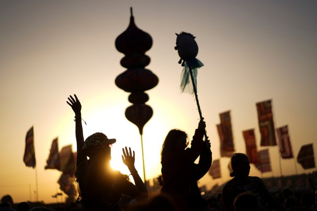 Festival goers dance in front of a setting sun at Glastonbury Festival
