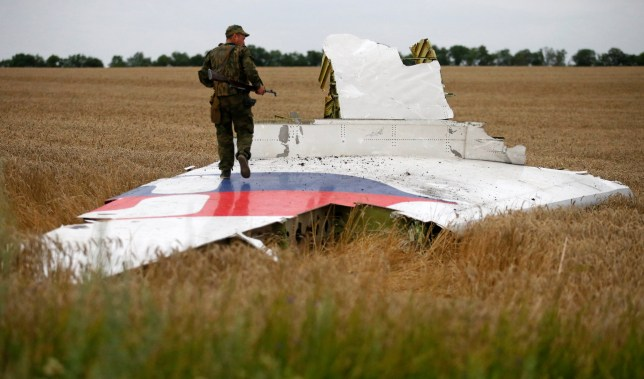 An armed pro-Russian separatist stands on part of the wreckage of the Malaysia Airlines Boeing 777 MH17