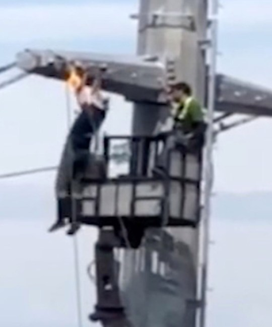 PIC BY Anthony Lafault / CATERS NEWS - (PICTURED: Footage showing an electrician hanging 40-metres high in the air from a set of high-voltage power lines completing a set of pull-ups in the city of Serpukhov, Russia) - A fitness fanatic took a quick break from his job in order to complete some pull-ups while hanging from a power line 40-metres in the air. Anthony Lafault, 26, was casually gazing out of his window in the city of Serpukhov, Russia, when a very unusual site caught his eye. Anthony spotted an electrician hanging 40-metres high in the air from a set of high-voltage power lines completing a set of pull-ups. The fitness fanatic completed a few sets of impressively dangerous and scary pull-ups, before safely lowering himself back onto a crane as his work colleague and Anthony looked on, shocked and amazed. SEE CATERS COPY