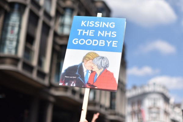 A placard showing Donald Trump kissing Theresa May with the slogan 'kissing the NHS goodbye'