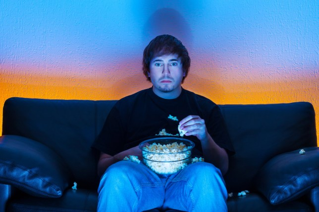 Man sitting in front of a TV with a bowl of popcorn