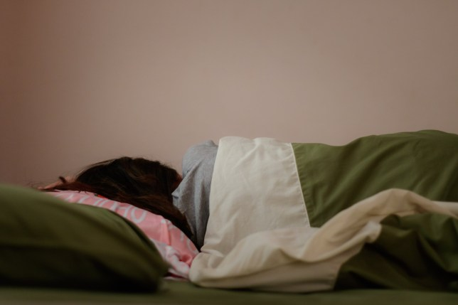 Young woman is sleeping from the back in bed