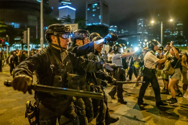 Police officers charge toward protesters after a rally against the extradition law proposal at the Central Government Complex in Hong Kong, China