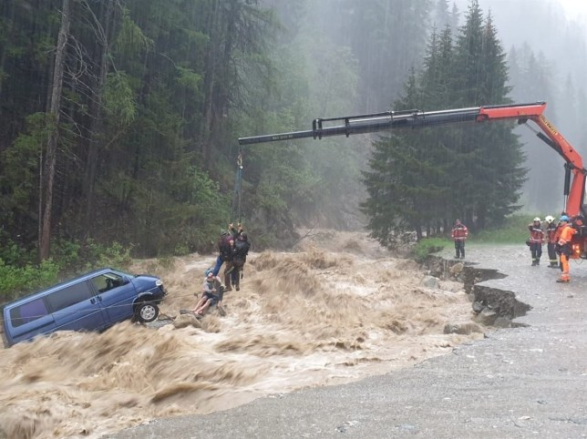 Two occupants of stranded van are lifted unhurt by a crane during heavy rain in this picture released June 12, 2019 by the Graubuenden Police in Spluegen, Switzerland. Picture taken June 12, 2019. Graubuenden Police/Handout via REUTERS ATTENTION EDITORS - THIS IMAGE WAS PROVIDED BY A THIRD PARTY