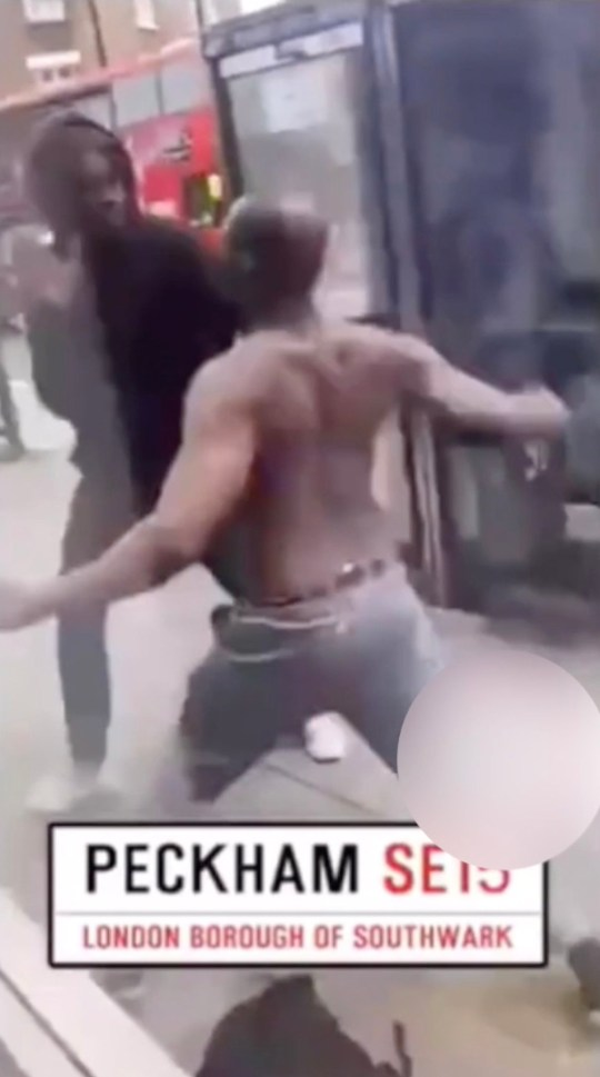 From another angle you can see the two men fighting on Peckham High St as crowd of onlookers gather, in footage posted to social-media yesterday (Wednesday 12th June, 2019). THIS is the shocking moment a violent brawl erupts between two men on a busy high street in broad daylight. Stunned shoppers scream in horror as a topless man and his opponent savagely punch, wrestle and kick each other to the ground. During the astonishing altercation, the shirtless male throws his opponent?s bag across the road and smashes straight into a passing bus ? before a group of passers-by are forced to break up the fight. The incident took place outside the Betfred store in Peckham High Street in Peckham, South London and the footage was posted online yesterday. It is unknown why the fight erupted between the pair. The video ? which is filmed by an onlooker who provides a running commentary on the fight ? begins by showing two males sparring with each in the middle of the high street. ... SEE COPY AND VID ? PIC BY NEWS DOG MEDIA ... 0121 517 0019 ... pictures@newsdogmedia.co.uk