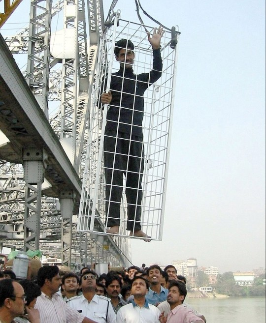 Caged Indian escape artist Chanchal Lahiri waves to the crowd before being lowered into the Hooghly river from Calcutta's Howrah Bridge February 24, 2002. Lahiri escaped from the locked cage about 15 seconds after it was submerged. REUTERS/Jayanta Shaw JS/JD - RP3DRHYOKUAB