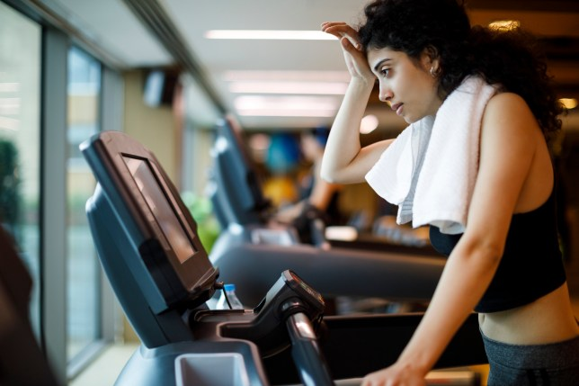 Woman looking tired on a treadmill, wiping sweat from her brow