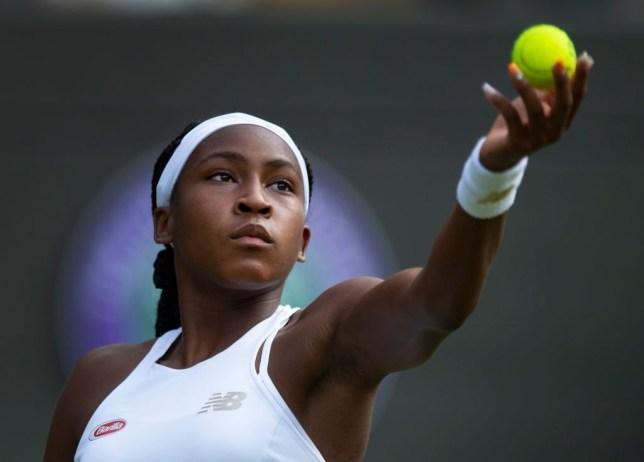 Cori Gauff throwing a tennis ball in the air against Venus Williams at Wimbledon