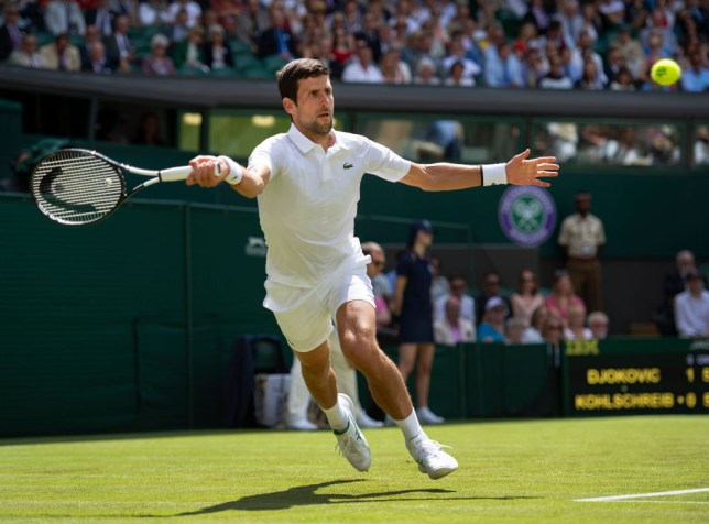 Novak Djokovic hitting a tennis ball with his racket on Centre Court at Wimbledon