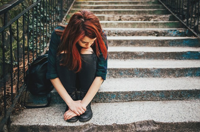 Depressed young woman sitting on stairs outdoors,