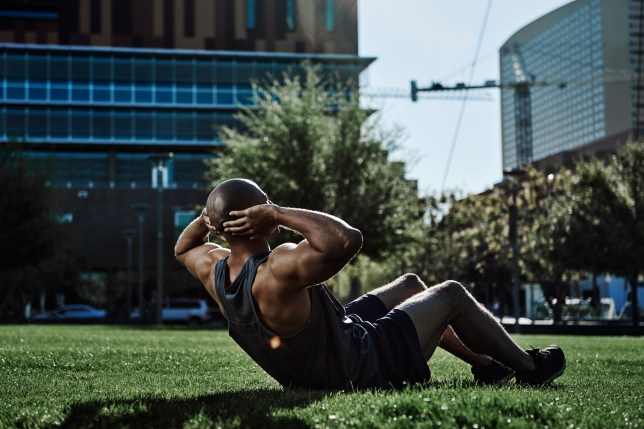 Male athlete doing sit-ups in a park
