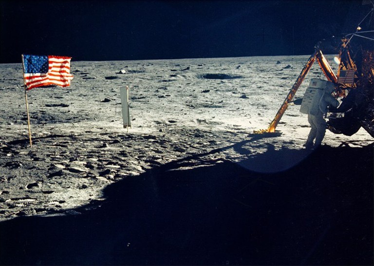 Neil Armstrong on the moon working on his space craft on the lunar surface