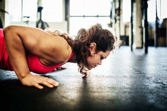 A woman doing a press up in the gym - her face close o the floor