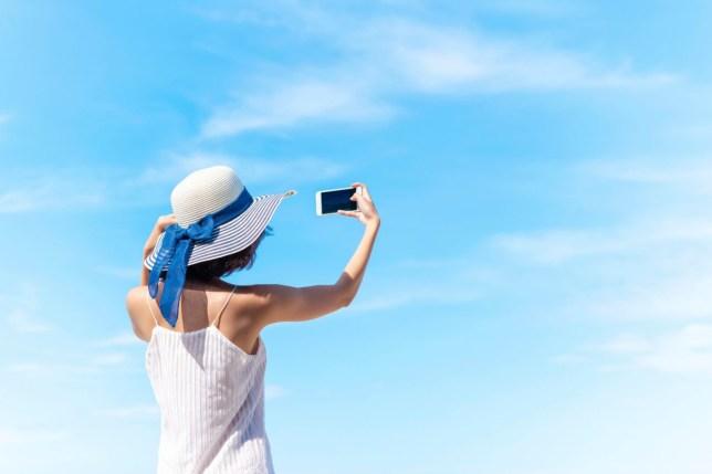 Happy summer trip on the beach. Woman selfie portrait with blue sky.