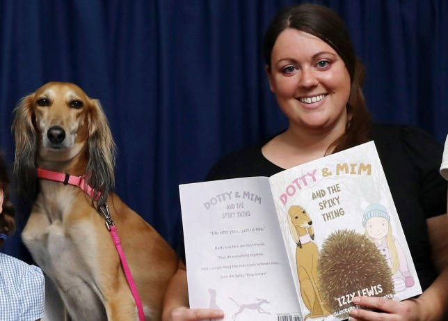 Pictured: Headteacher Miss Izzy Lewis with Mim the greyhound and her book, Dotty Mim and the Spikey Thing. A headteacher at a cash-strapped primary school has resorted to writing her own children's book in a bid to raise desperately needed funds. Izzy Lewis decided to pen her own children's story when budget cuts meant she had to start appealing to parents to donate money to her school to fund projects. The English teacher and head of St Jude's primary school in Portsmouth, Hants, has been running a series of fundraising events in recent months. Now she hopes her story, Dotty Mim and the Spikey Thing, will help raise ??3,000 to cover the cost of new IT equipment, among other things. SEE OUR COPY FOR DETAILS. ?? Portsmouth News/Solent News & Photo Agency UK +44 (0) 2380 458800