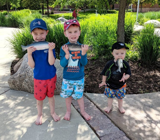 Two older boys hold rubber fish in their hands and their younger brother Landon puts it in his mouth
