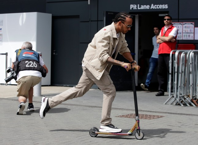 Mercedes driver Lewis Hamilton of Britain rides a scooter in the paddock of the Silverstone racetrack