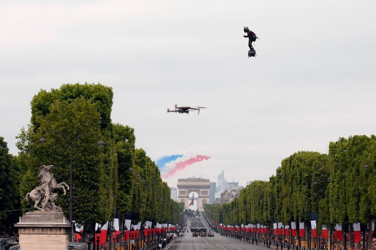 "Zapata CEO Franky Zapata flies a jet-powered hoverboard or ""Flyboard"" as French elite acrobatic flying team ""Patrouille de France"" (PAF) flies over the Arc de Triomphe during the Bastille Day military parade down the Champs-Elysees avenue in Paris on July 14, 2019. (Photo by Lionel BONAVENTURE / AFP)LIONEL BONAVENTURE/AFP/Getty Images"