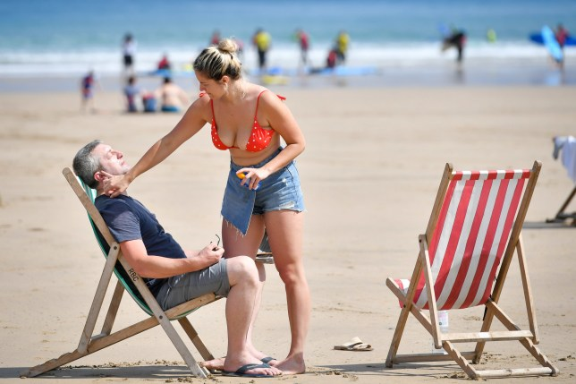 Sunbathers apply sunscreen during the hot summer weather