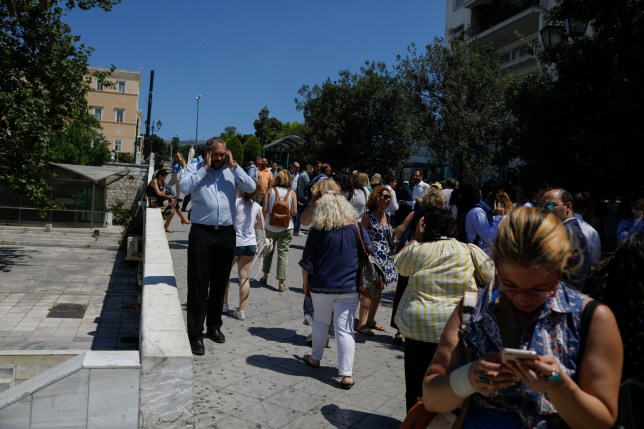 People speak on their phones as they stand outside the building they work in, after a strong earthquake hit near the Greek capital of Athens, Friday, July 17, 2019. The Athens Institute of Geodynamics gave the earthquake a preliminary magnitude of 5.1 but the U.S. Geological Survey gave it a preliminary magnitude of 5.3. The Athens Institute says the quake struck at 2:38 p.m. local time (1113 GMT) about 26 kilometers (13.7 miles) north of Athens. (AP Photo/Petros Giannakouris)