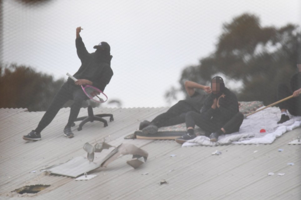 epa07732521 Detainees in action during a riot at the Frank Baxter Juvenile Justice Centre in Kariong, Australia, 22 July 2019. A riot broke out at a New South Wales juvenile justice center on the Central Coast after numerous inmates escaped from their cells and attacked staff. Several inmates climbed onto the roof of the facility and five inmates were stabbed during the melee. Police officers were able restore order after several hours. EPA/DEAN LEWINS AUSTRALIA AND NEW ZEALAND OUT - IMAGES PIXELLATED AT SOURCE