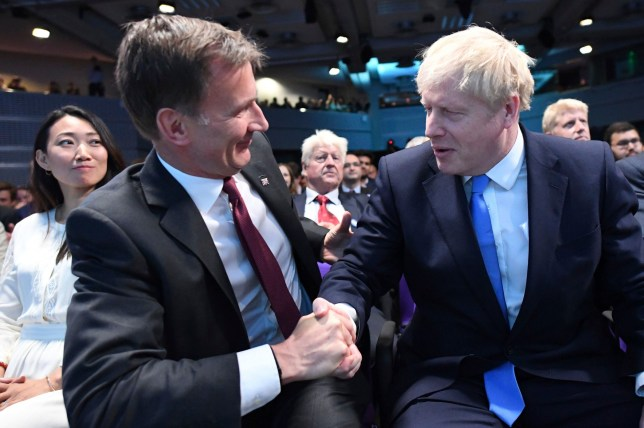 """Jeremy Hunt, left, congratulates Boris Johnson after the announcement of the result in the ballot for the new Conservative party leader, in London, Tuesday, July 23, 2019. Brexit hardliner Boris Johnson won the contest to lead Britain's governing Conservative Party on Tuesday and will become the country's next prime minister, tasked with fulfilling his promise to lead the U.K. out of the European Union """"come what may."""" (Stefan Rousseau/Pool photo via AP)"""