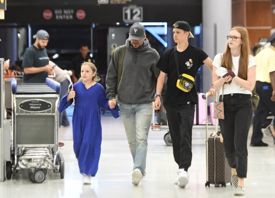 EXCLUSIVE: David and Victoria Beckham walk through Miami airport after a week in the Florida sunshine. The couple were accompanied by three of their children, sons, Romeo, 16, and Cruz, 14, as well as daughter Harper, eight. They jetted home to England after an action-packed week in Miami, where former England captain David spent much of his time working on his Inter Miami CF soccer team plans. The Beckhams visited a water-park, went fishing at sea, and the children played beach soccer. 21 Jul 2019 Pictured: David Beckham; Victoria Beckham. Photo credit: MEGA TheMegaAgency.com +1 888 505 6342 (Mega Agency TagID: MEGA470660_023.jpg) [Photo via Mega Agency]