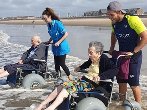 Elderly pair giggle like children as they get chance to dip their toes in the sea