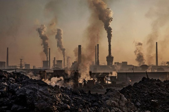 Smoke billows from a large steel plant as a Chinese labourer works at an unauthorized steel factory in Inner Mongolia, China. (Photo by Kevin Frayer/Getty Images)