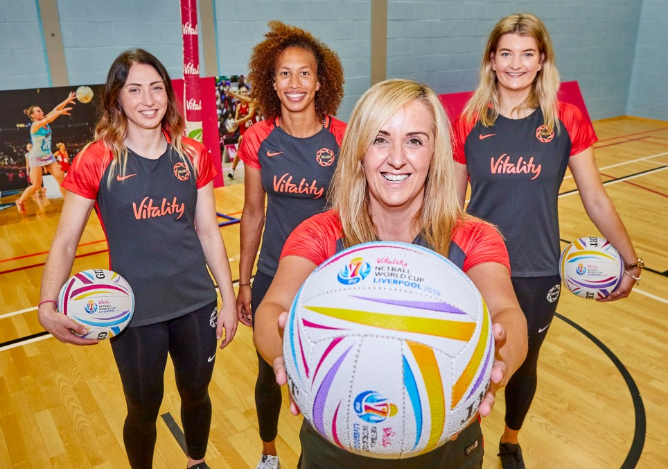Tracey Neville holds a netball up to the camera. Serena Guthrie, Jade Clarke and Fran Williams stand behind her.