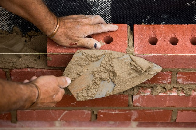 A bricklayer putting cement onto bricks at a residential construction site