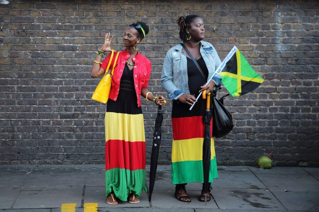 Two women standing on the street dressed in Jamaica flag colours on Jamaica Independence Day in Brixton, 2012